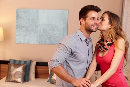 be kissed: Giovani coppie che baciano nella camera di albergo all'arrivo.