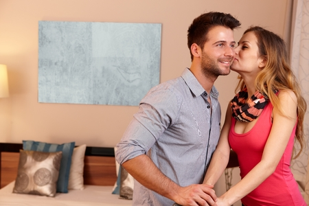 be kissed: Young couple kissing in hotel room upon arrival.