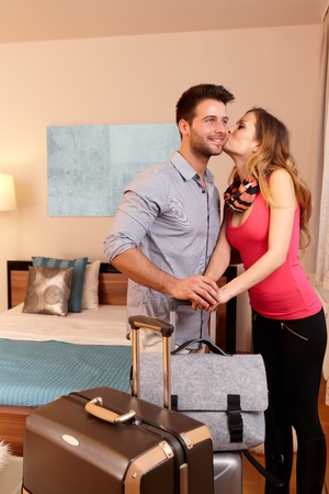be kissed: Young couple kissing upon arrival to hotel room.