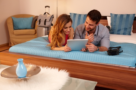 Young couple using tablet in hotel room, lying on bed.
