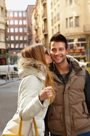 weekend break: Happy couple kissing in the city at wintertime, smiling. Stock Photo