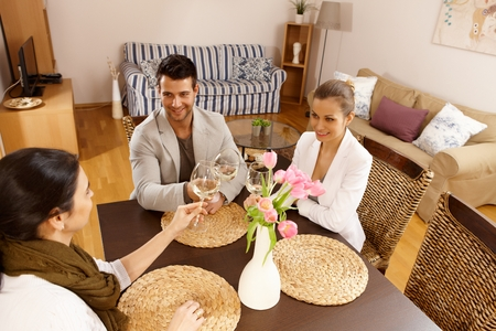 companionship: Young companionship sitting at table, clinking glasses at home. Stock Photo