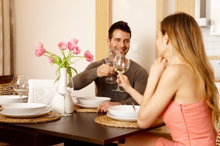 treating: Young couple clinking glasses at home while having dinner, smiling. Stock Photo
