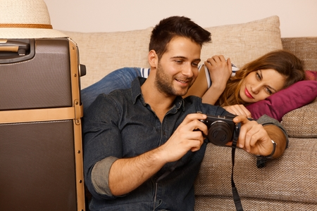 taken: Young couple looking at photos taken on holiday before leaving.