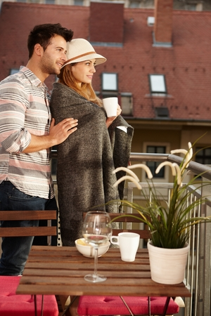 Young couple searching distance from balcony, embracing. photo