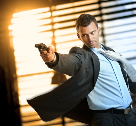 Determined caucasian action hero wearing suit and tie holding gun in hand. Standing, moving, aiming with revolver, inspector, cop, police, policeman, indoor, thriller, crime. Stock Photo