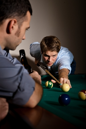 cue sports: Young casual caucasian man concentrating hard on strike at billiard game with friend. Holding cue ready to strike the ball. Stock Photo