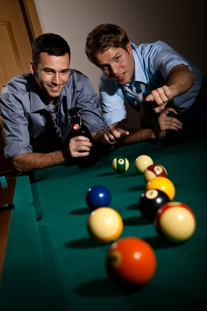 Happy friends discussing a game of billiard at table with beer in hand. Selective focus, pointing. Having fun. photo