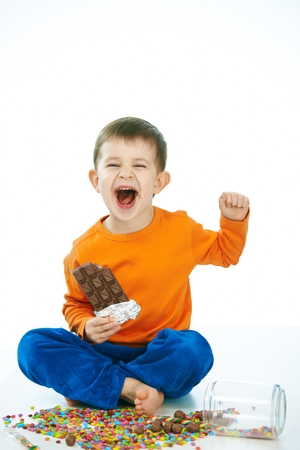 6 7 years: Naughty little kid eating chocolate sitting cross-legged on floor, sweets spilt. Laughing, hand in hair, isolated on white. Stock Photo