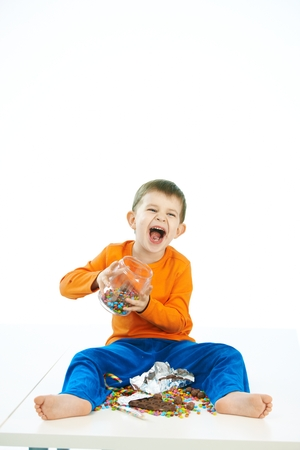 Mischievous little boy with sweets jar sitting on floor. Laughing, jar in hand, bare feet, isolated on white. photo