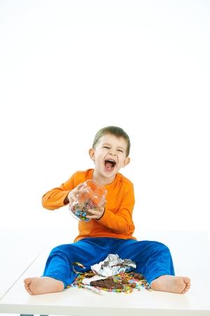 Malizioso ragazzo con i dolci vaso seduta sul pavimento. Ridere, vaso in mano, piedi nudi, isolato su bianco.