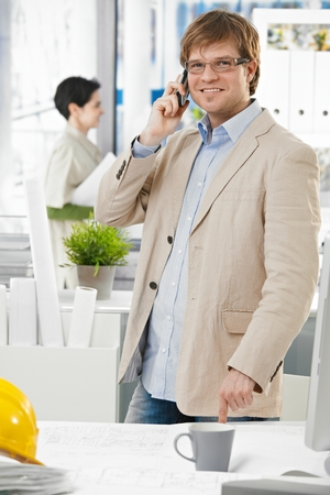 Happy smiling caucasian architect at bright office talking on mobile phone, pointing at table, standing. Suit no tie, looking at camera. photo
