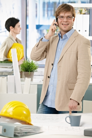 Happy caucasian architect standing with hardhat at office talking on phone. Smiling, looking up, pointing at table. photo