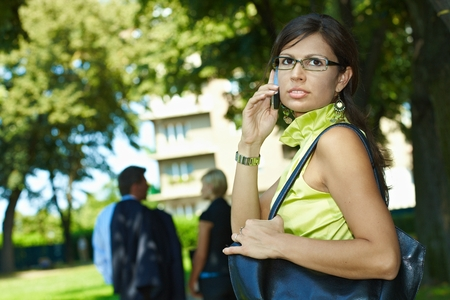 Busy caucasian businesswoman making a mobile phone call on the street, outdoor. Wearing glasses, shoulder bag, looking back. photo