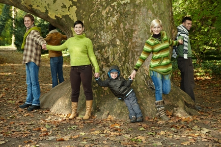 hands holding tree: Happy casual friends hiking in forest holding hands in a ring around tree at outdoor park. Smiling, happy, on holiday, looking at camera, fall. Stock Photo