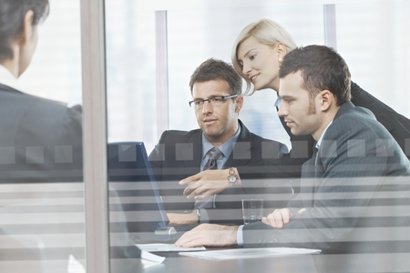 Focused caucasian business people meeting in boardroom behind glass. Sitting at table, wearing suit, looking at screen, pointing. Stock Photo - 30996292