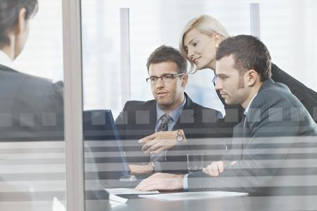 Gericht blanke mensen uit het bedrijfsleven bijeenkomst in de bestuurskamer achter glas. Zitten aan tafel, dragen pak, kijken naar scherm, wijzend.