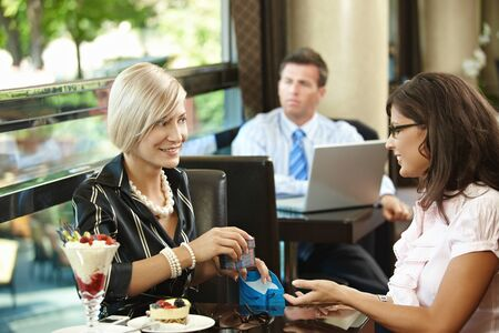 fancy box: Elegant blonde caucasian businesswoman giving gift at restaurant. Sitting at table, smiling, gift box in hand, ice cream on table, indoor. Stock Photo