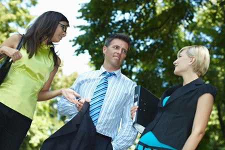 Business people having a discussing outdoor. Smiling, happy, standing gesturing, jacket and file folder in hand. Low angle view. photo