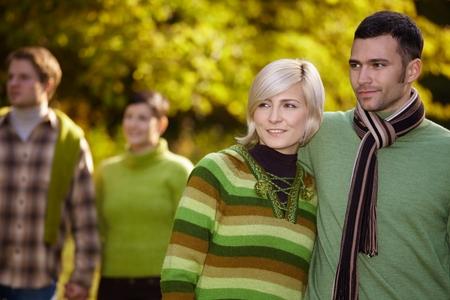 warm clothes: Felice casual coppia caucasica con amici camminando all'aperto. Sorridere, indossando vestiti caldi in autunno. Archivio Fotografico