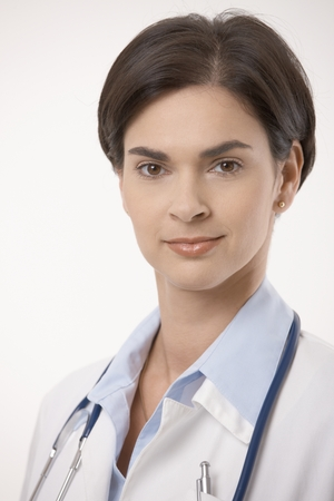Close up portrait of female caucasian doctor in lab coat. Smiling, looking at camera, isolated on white. photo