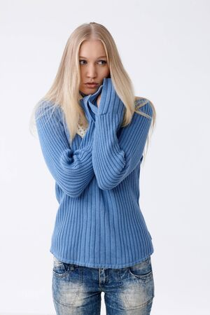 Young woman in pullover freezing or frightened, folding arms defensively, looking scared. photo