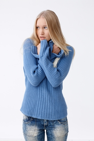 folding arms: Young blonde woman freezing or frightened, folding arms defensively, looking away.