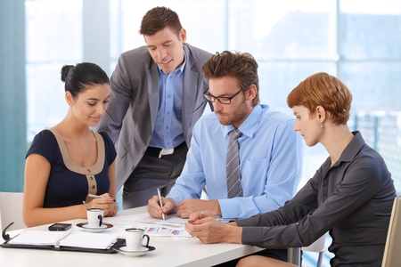 female boss: Business team meeting at office table with boss. Writing on paper, wearing suit and glasses, sitting at table, businessman, businesswoman, personal organizer, morning coffee.
