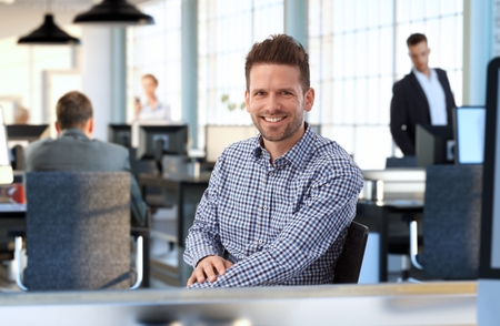 Casual man at sitting at desk in office smiling. photo