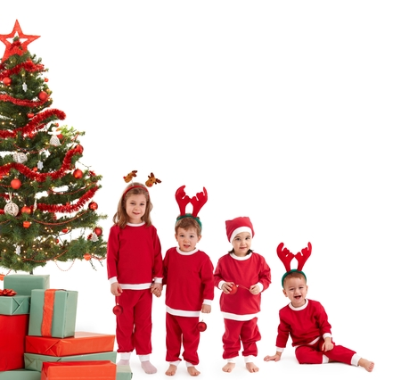 Small kids in red with christmas tree and presents, isolated on white. Group, smiling, laughing, having fun, looking at camera. photo