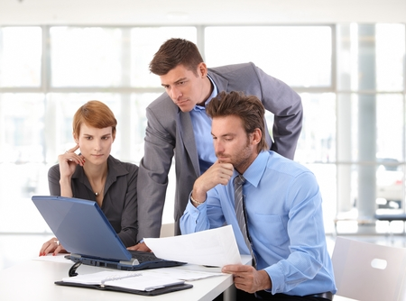 Business team meeting using laptop at office. Standing, sitting, looking at screen, serious, wearing suit. Hand under chin, papers on table.