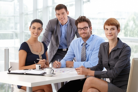 Portrait of happy caucasian business team sitting at corporate office table, wearing suit, looking at camera, smiling. Paperwork on table.