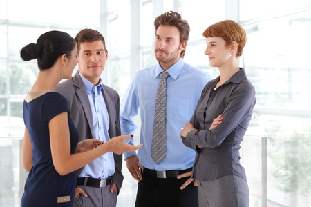business lounge: Corporate people chatting at business office lobby. Standing, gesturing, arms crossed, arms on hip, confident, wearing suit, confident.