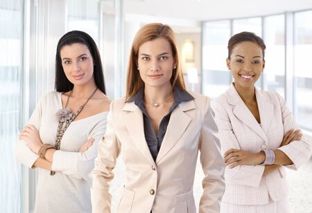 Group portrait of attractive elegant businesswoman. Standing, smiling, looking at camera, arms crossed. Bright background.