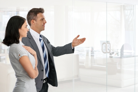 Happy caucasian businessman in suit presenting new possibility, achievement with hand to businesswoman at business office. Standing, copyspace. photo