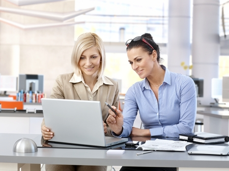co workers: Happy businesswomen sitting at desk working together with laptop in modern office. Stock Photo