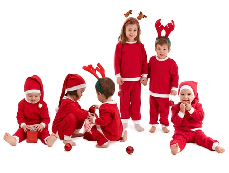 Group of cute caucasian kids playing in christmas red suit cutout, isolated on white. Smiling, having fun. photo