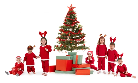Cute kids in red with christmas tree and presents, isolated on white. Group, smiling, laughing, having fun, looking at camera. photo