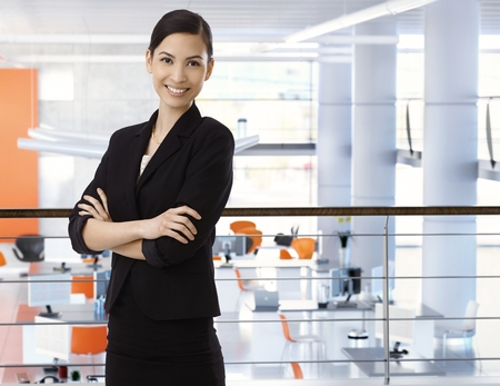 Attractive, happy, asian businesswoman at high-tech business office with arms crossed. Smiling, arms crossed, standing upstairs. Copyspace. Stock Photo