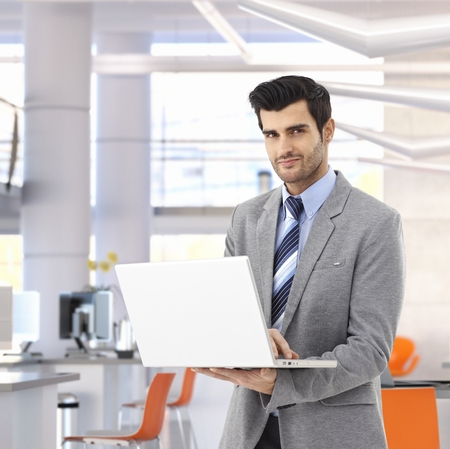 Confident caucasian businessman working on laptop computer at bright business office. Suit, small smile, standing.