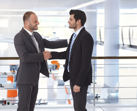 Happy guapo caucásico erizados de negocios que sacuden las manos en acuerdo de negocios en la oficina. Mano sobre el hombro, vista lateral, copyspace, traje.