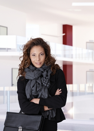 Trendy casual female office worker at business center, standing, smiling, arms crossed, looking at camera. photo