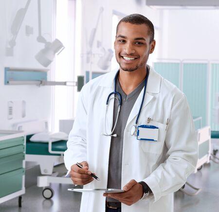 bata de laboratorio: Feliz m�dico sonriente afro americano en la habitaci�n del hospital con la tableta, Mirando a la c�mara, de pie, vestido con estetoscopio y bata de laboratorio.