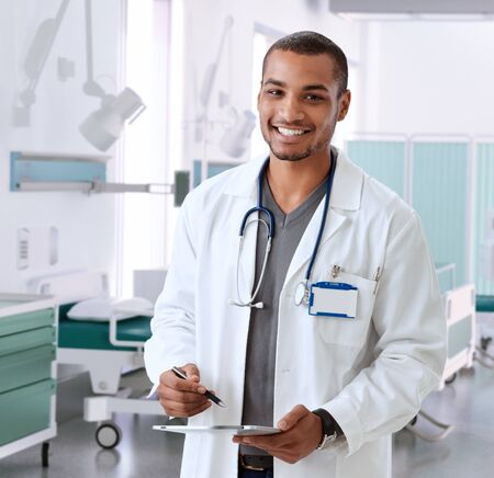 computer lab: Happy smiling afro american doctor at hospital room with tablet, Looking at camera, standing, wearing stethoscope and lab coat. Stock Photo