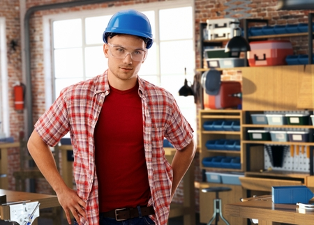 journeyman: Young casual caucasian man with hardhat at workshop. Standing, safety goggles.