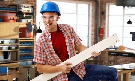 air guitar: Happy casual caucasian man in hardhat having fun at DIY workshop. Smiling, standing, air guitar.