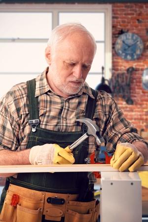 Senior caucasian handyman hammering at DIY home workshop. Working, focused. photo