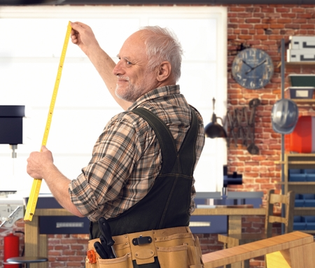 Happy casual senior handyman measuring with folding ruler at workshop. Smiling with back to camera.