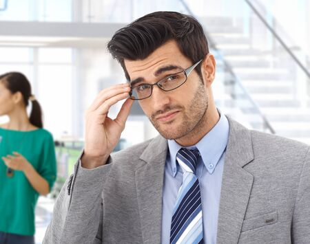 bristly: Smart handsome young caucasian bristly business expert with glasses at office. Confident, looking at camera, suit and tie.