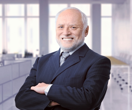 Portrait of happy caucasian senior business executive advisor at office. Smiling, successful, suit and tie, looking at camera, arms crossed.